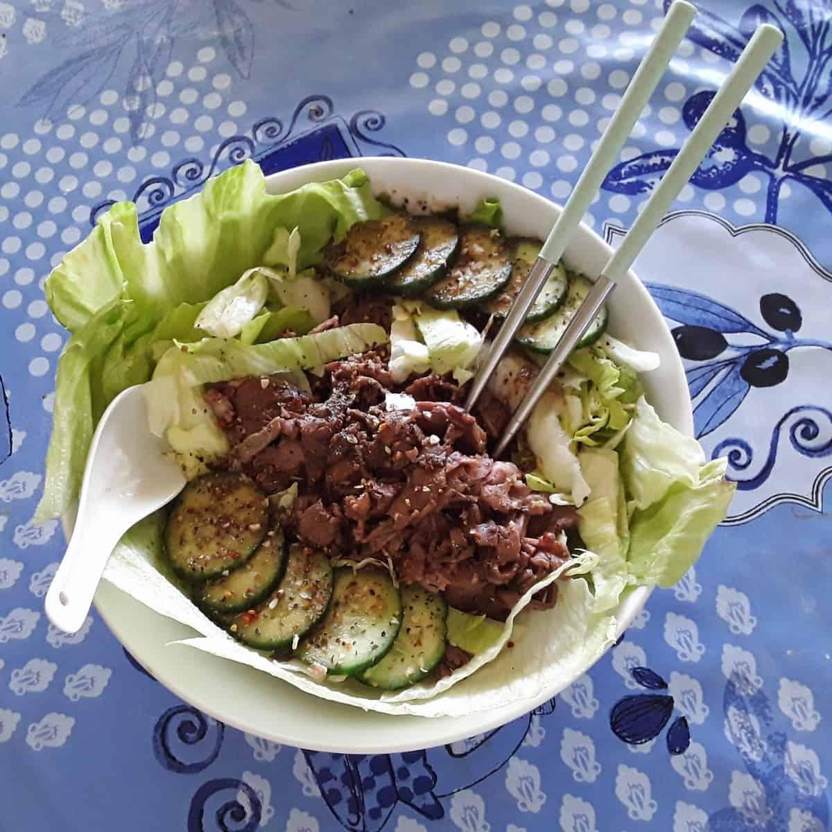 Thai beef salad in white bowl with chopsticks.