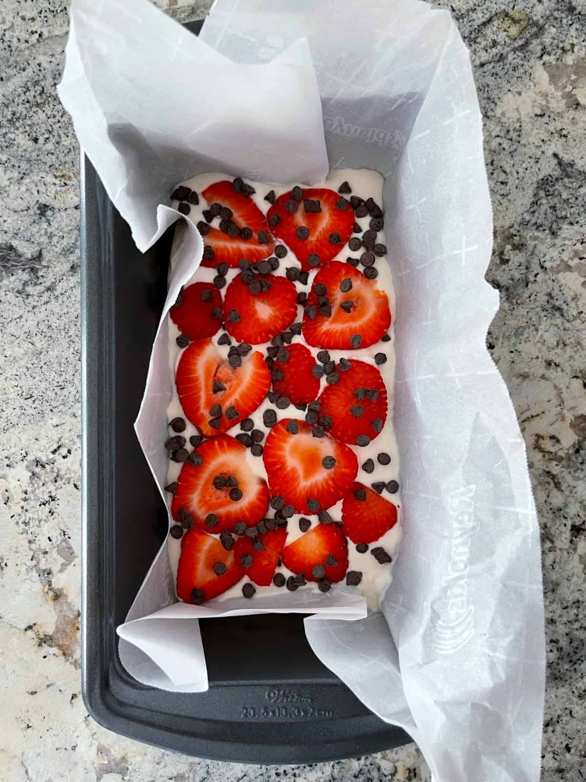 Strawberry chocolate chip yogurt bark in parchment-lined loaf pan on granite counter.