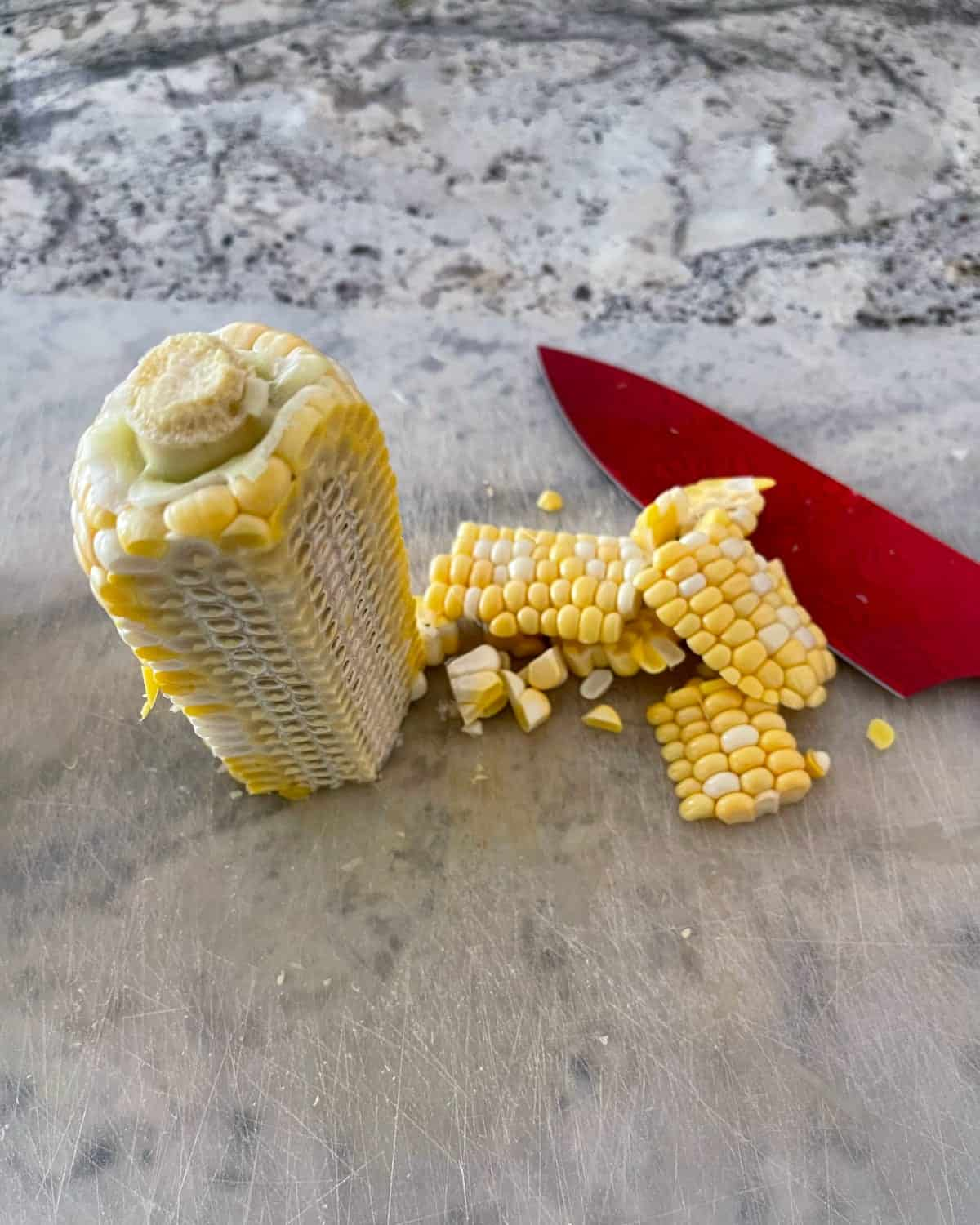 Removing corn kernels from half of corn cob with red knife.