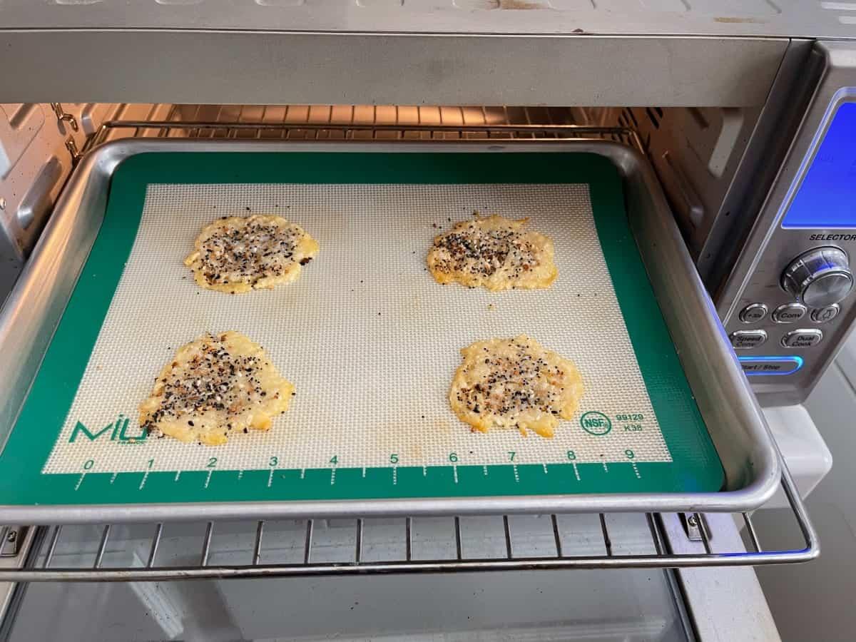 Baking everything bagel seasoned Parmesan cheese crisps on baking pan in toaster oven.