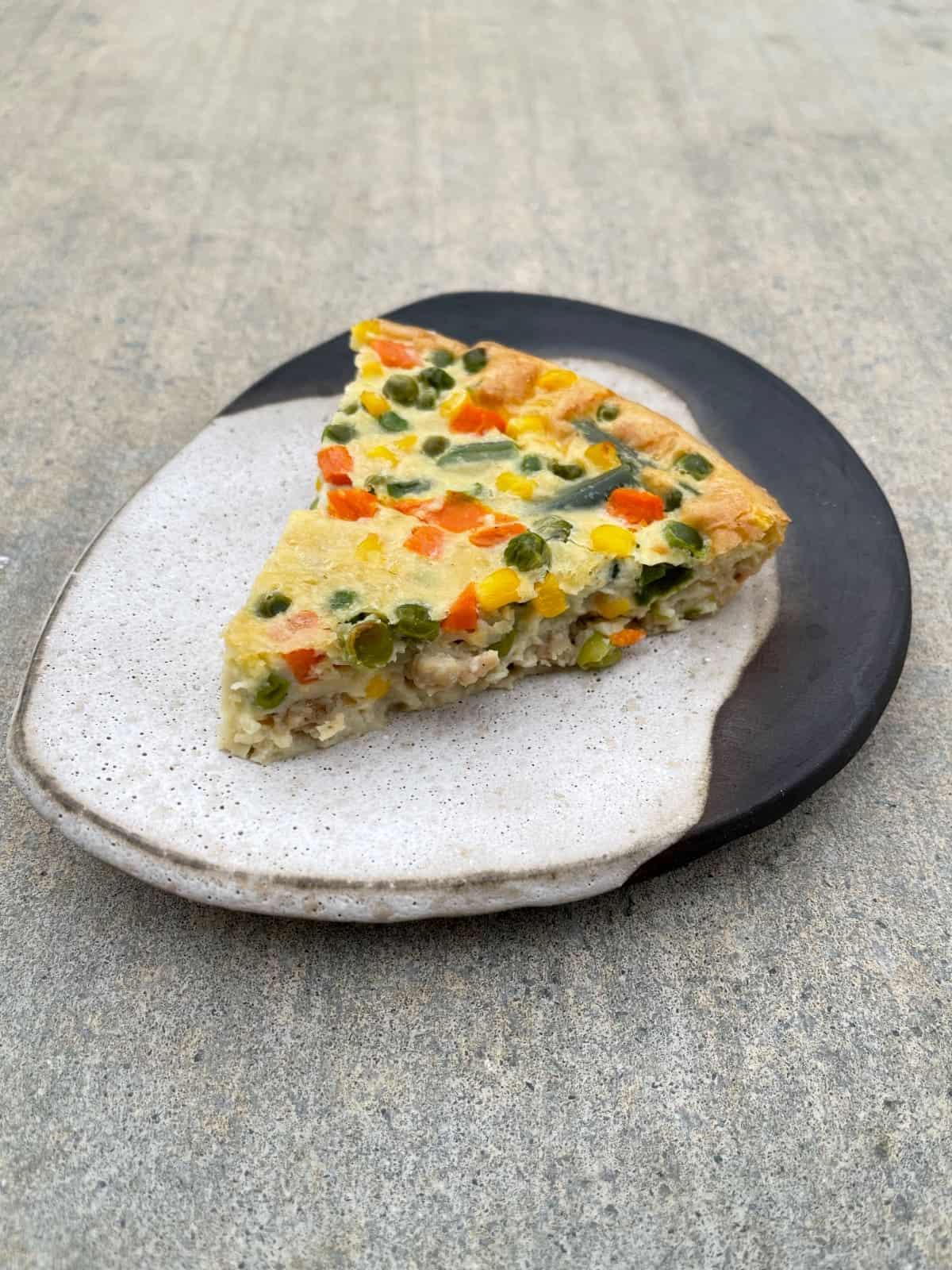 Slice of Chicken Sausage Pie on ceramic plate.