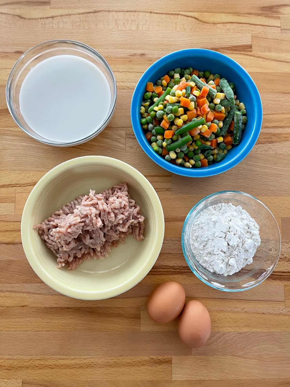 Ingredients for making Impossible Sausage Pie including milk, frozen vegetables, bulk chicken sausage, Bisquick and two eggs on wooden table.