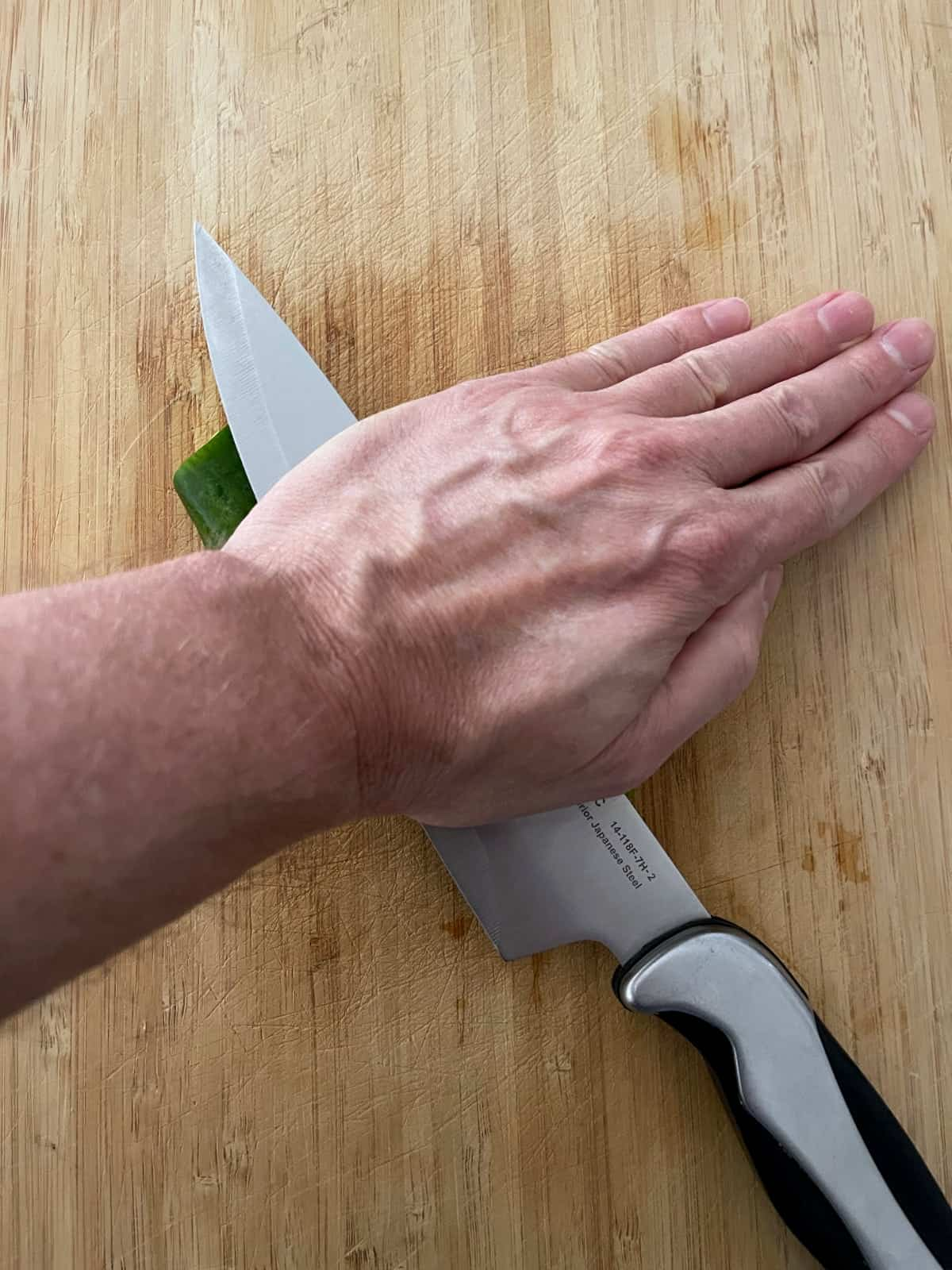 Pressing chef's knife over mini Persian cucumber on wooden cutting board.
