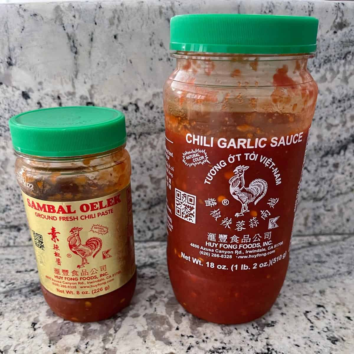 Bottle of Sambal Oelek next to bottle of Chili Garlic Sauce on granite counter.