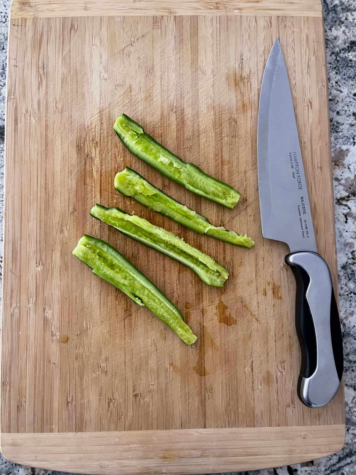 Smashed cucumber pieces alongside chef's knife on wood cutting board.
