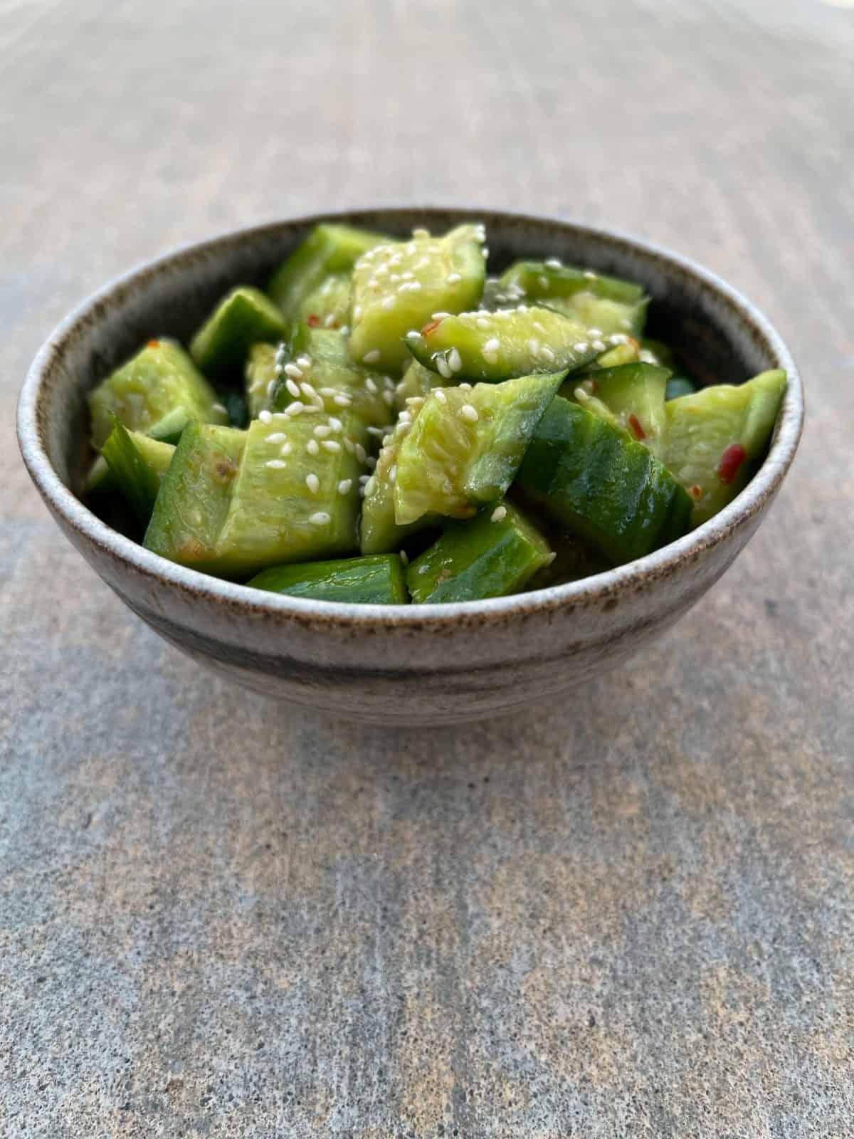 Spicy sesame cucumber salad in ceramic bowl.