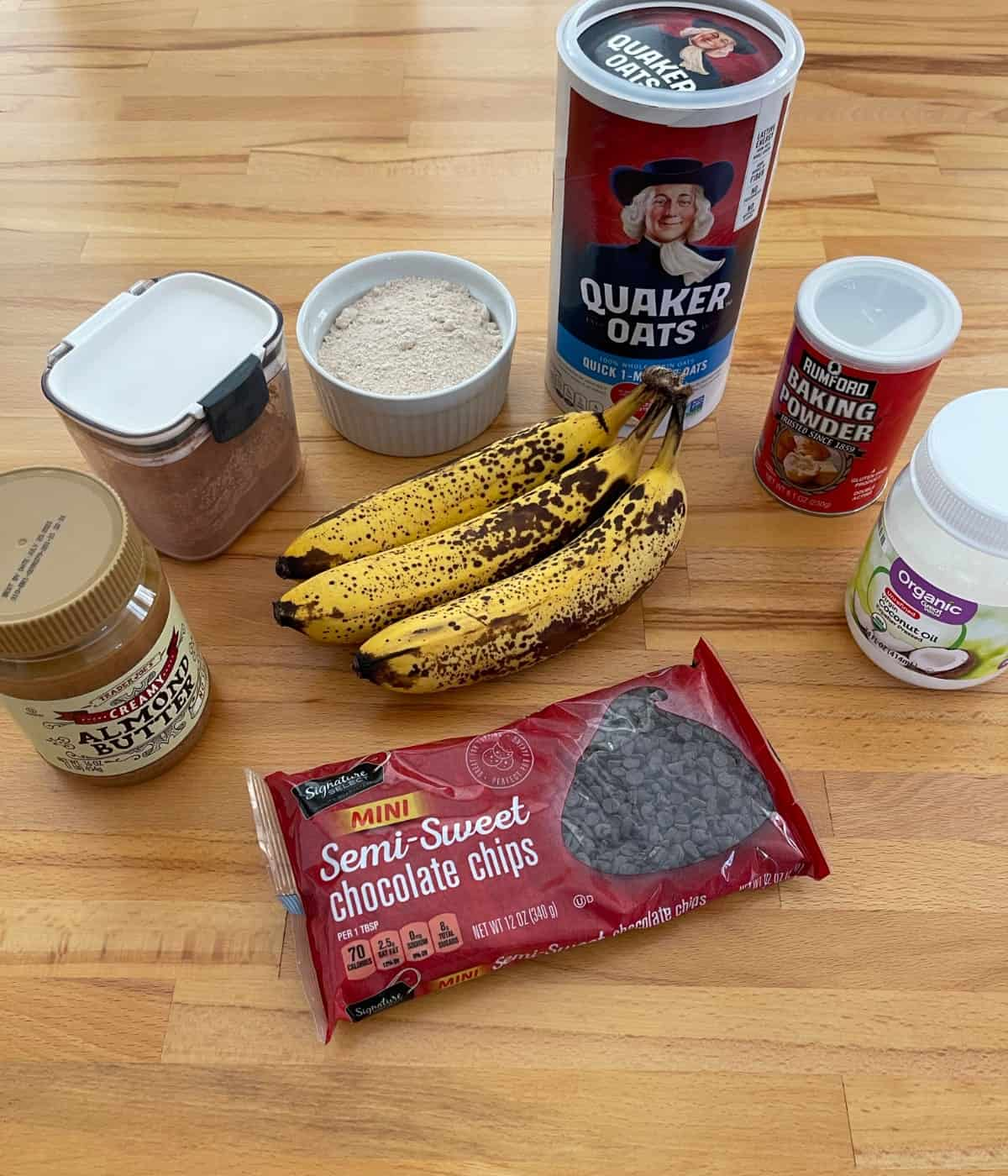 Ingredients for making banana bread brownies, including bananas, mini chocolate chips, almond butter, cocoa powder, flour, oats and coconut oil.