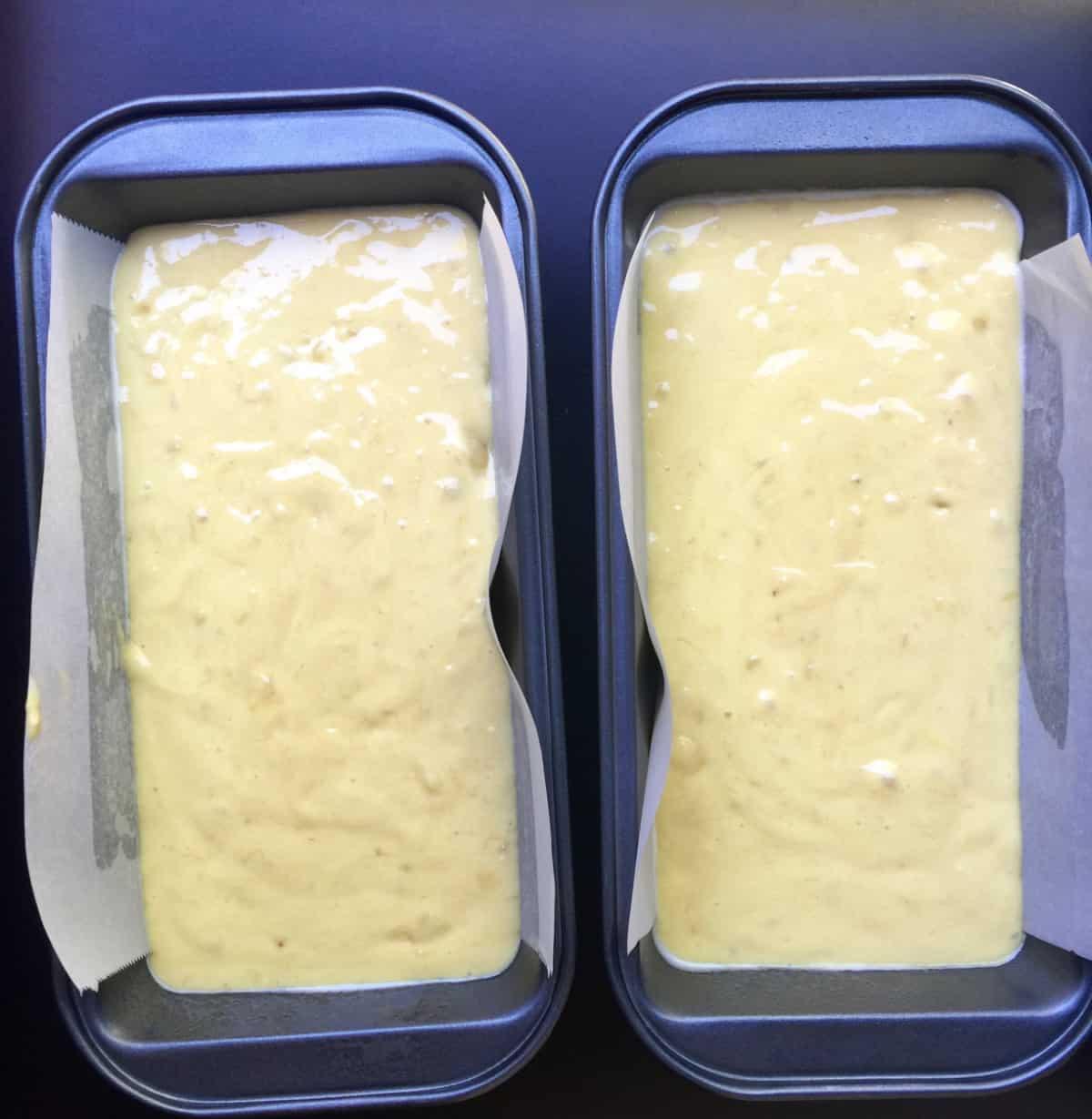 Banana bread batter in two loaf pans.