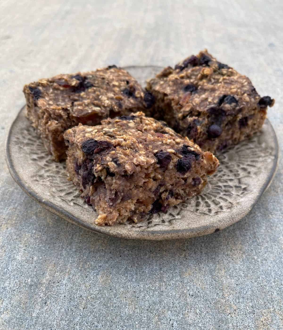 Blueberry banana baked oatmeal squares on ceramic plate.