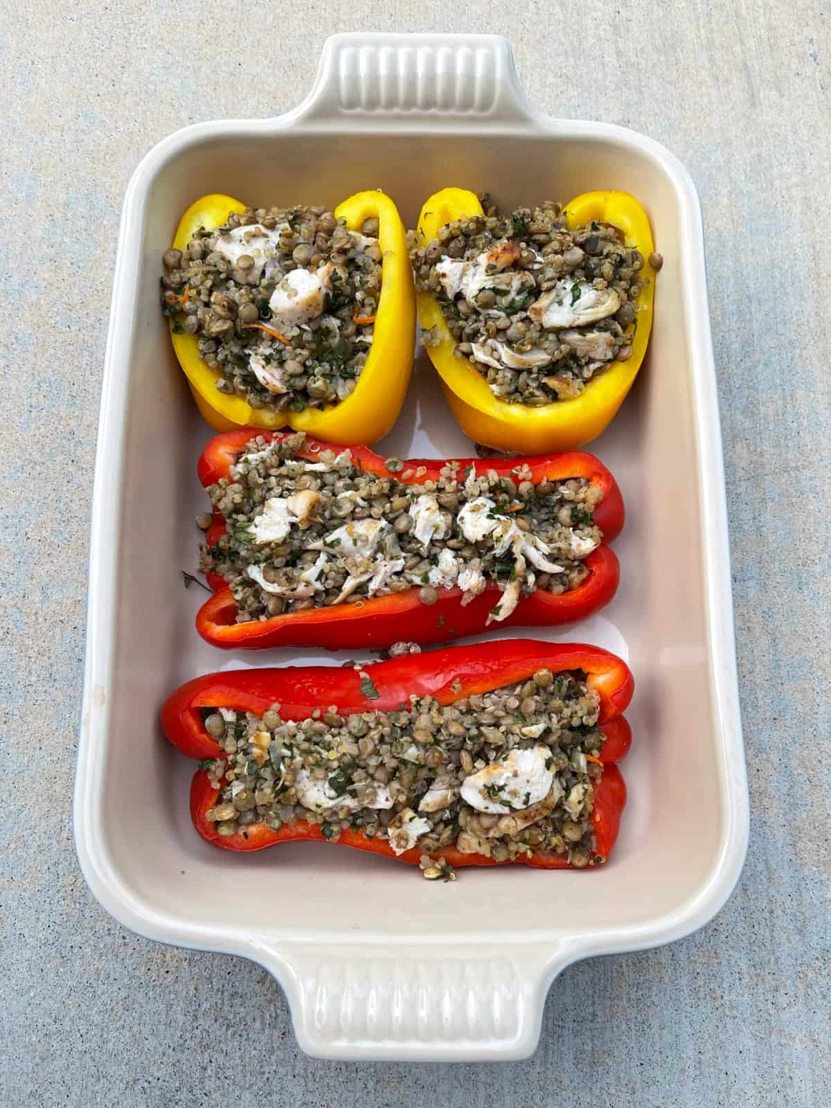 Leftover Mediterranean lentil and quinoa stuffed peppers in baking dish.