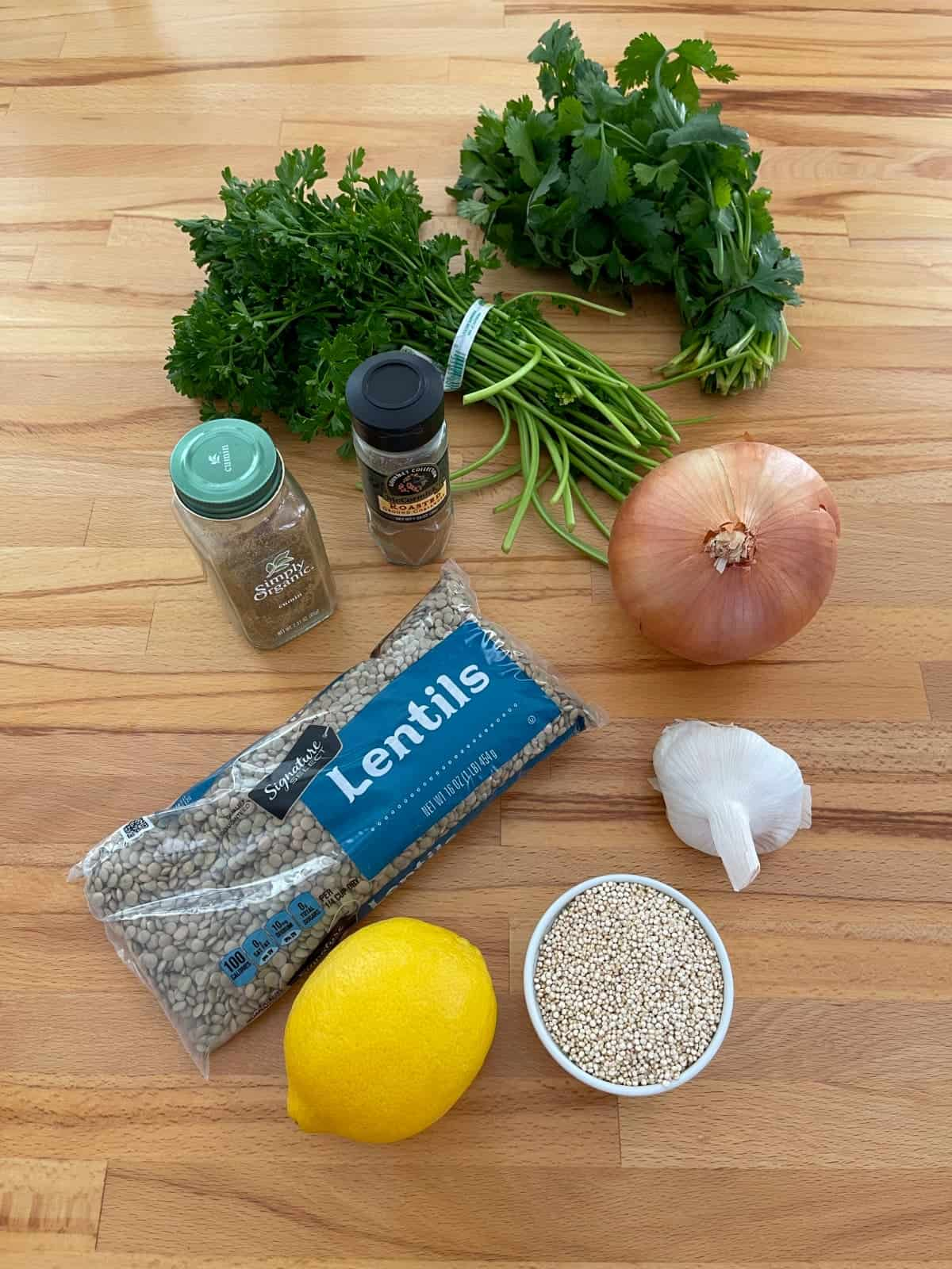 Bag of lentils, quinoa, lemon, garlic, onion, bunches of parsley and cilantro and jars of coriander and cumin of wood table.
