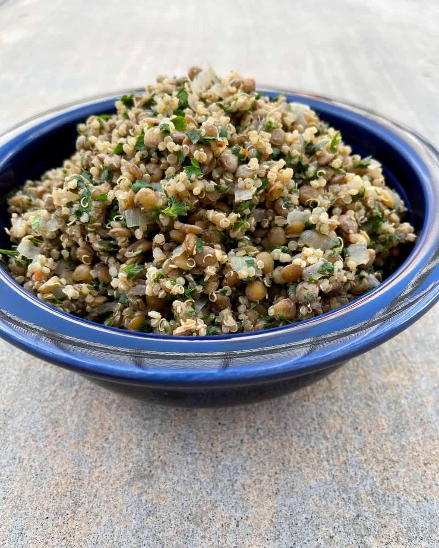 Vegetarian Mediterranean lentils and quinoa in blue bowl.