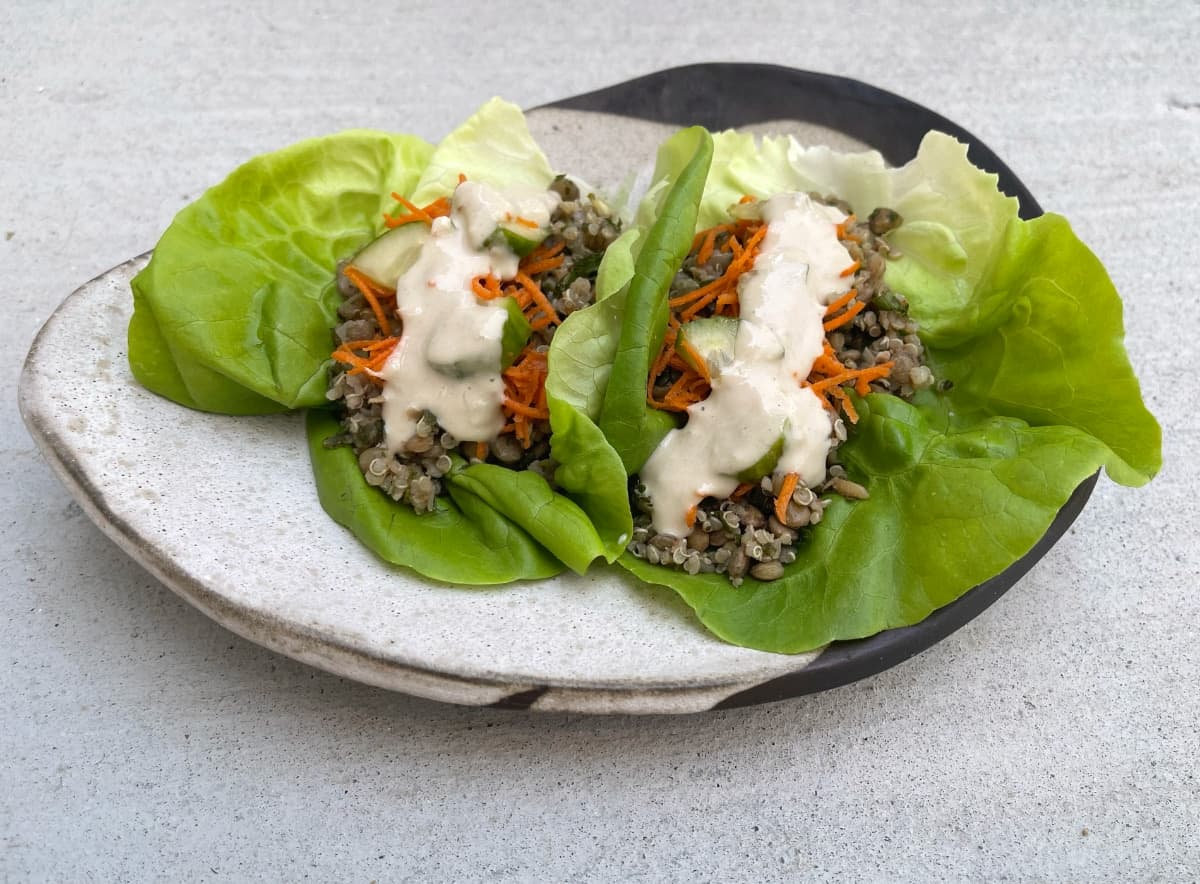 Two vegetarian Mediterranean lettuce wraps with quinoa and lentils on ceramic plate.
