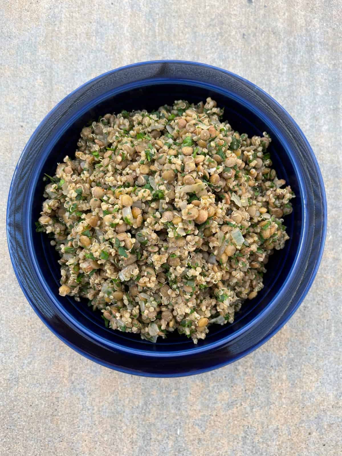 Mediterranean lentil quinoa lettuce wraps served family-style in blue bowl.