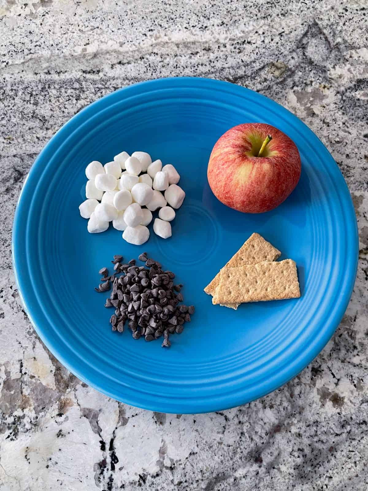 Mini marshmallows, chocolate chips, two graham crackers and whole apple on blue plate on granite.