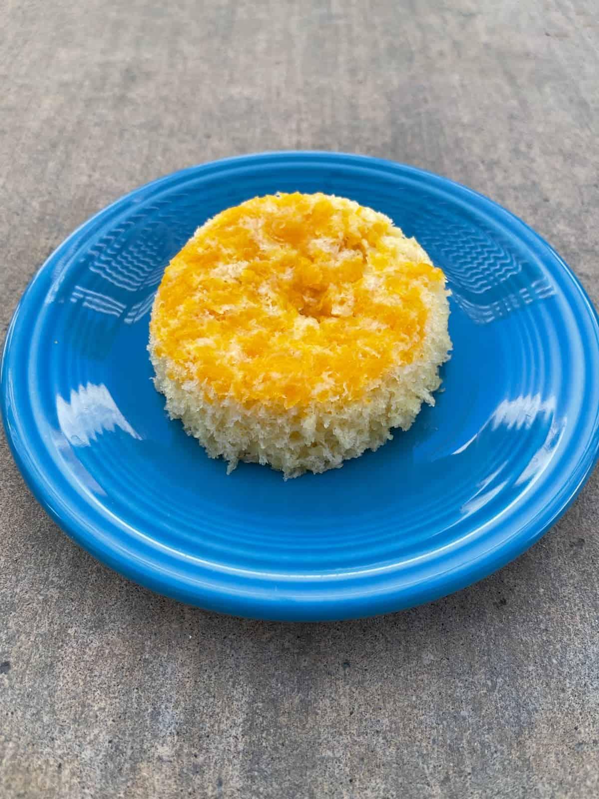 Orange angel food cake on small blue plate.