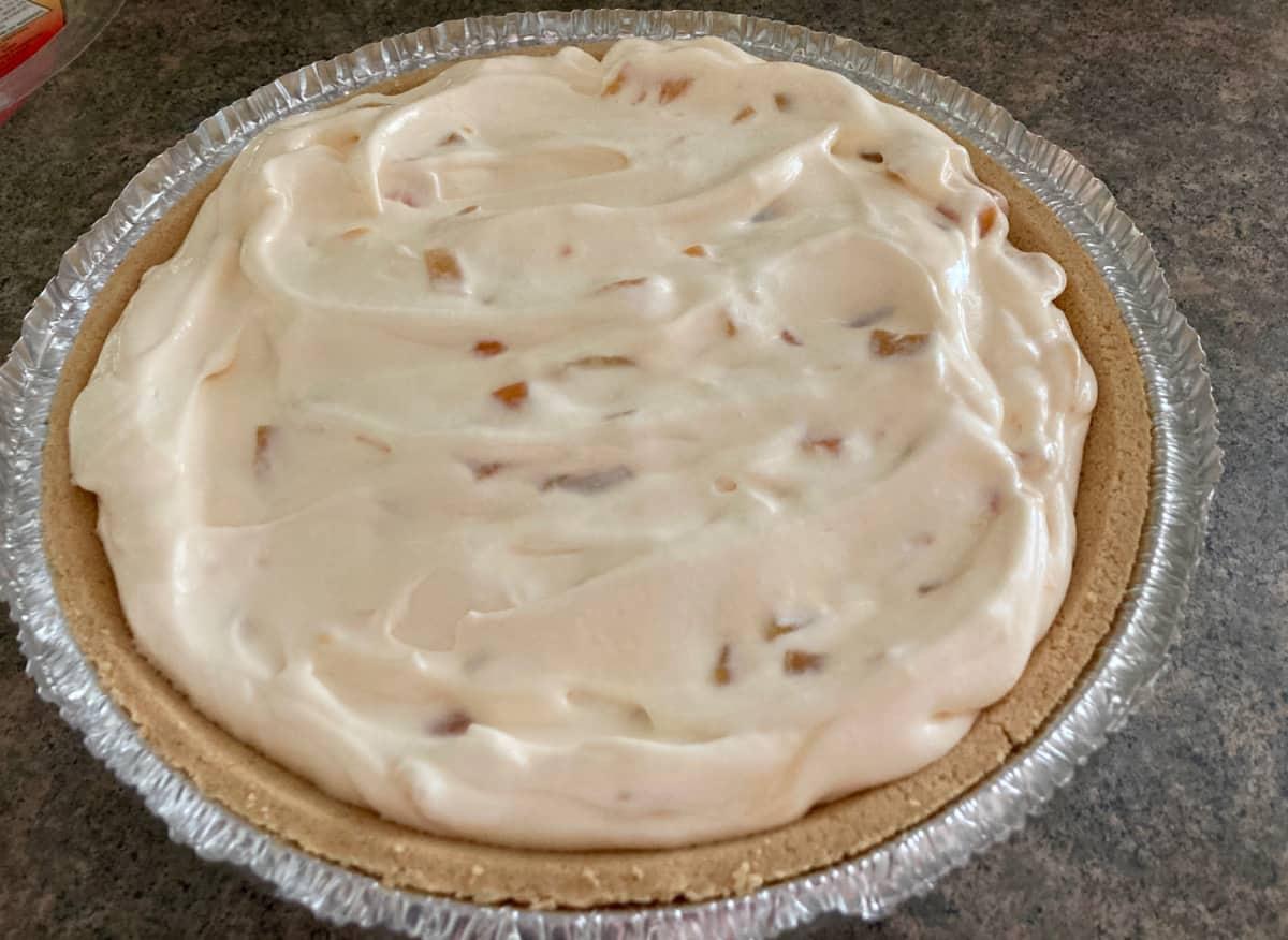 Whole creamy peach yogurt pie in graham cracker crust.