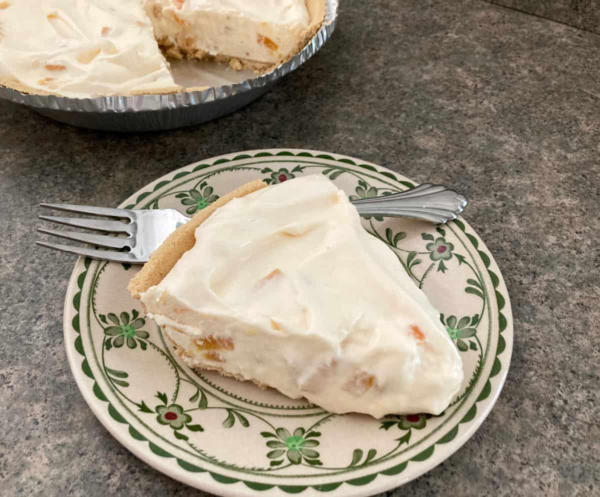 Slice of creamy peach frozen yogurt pie on plate with fork.