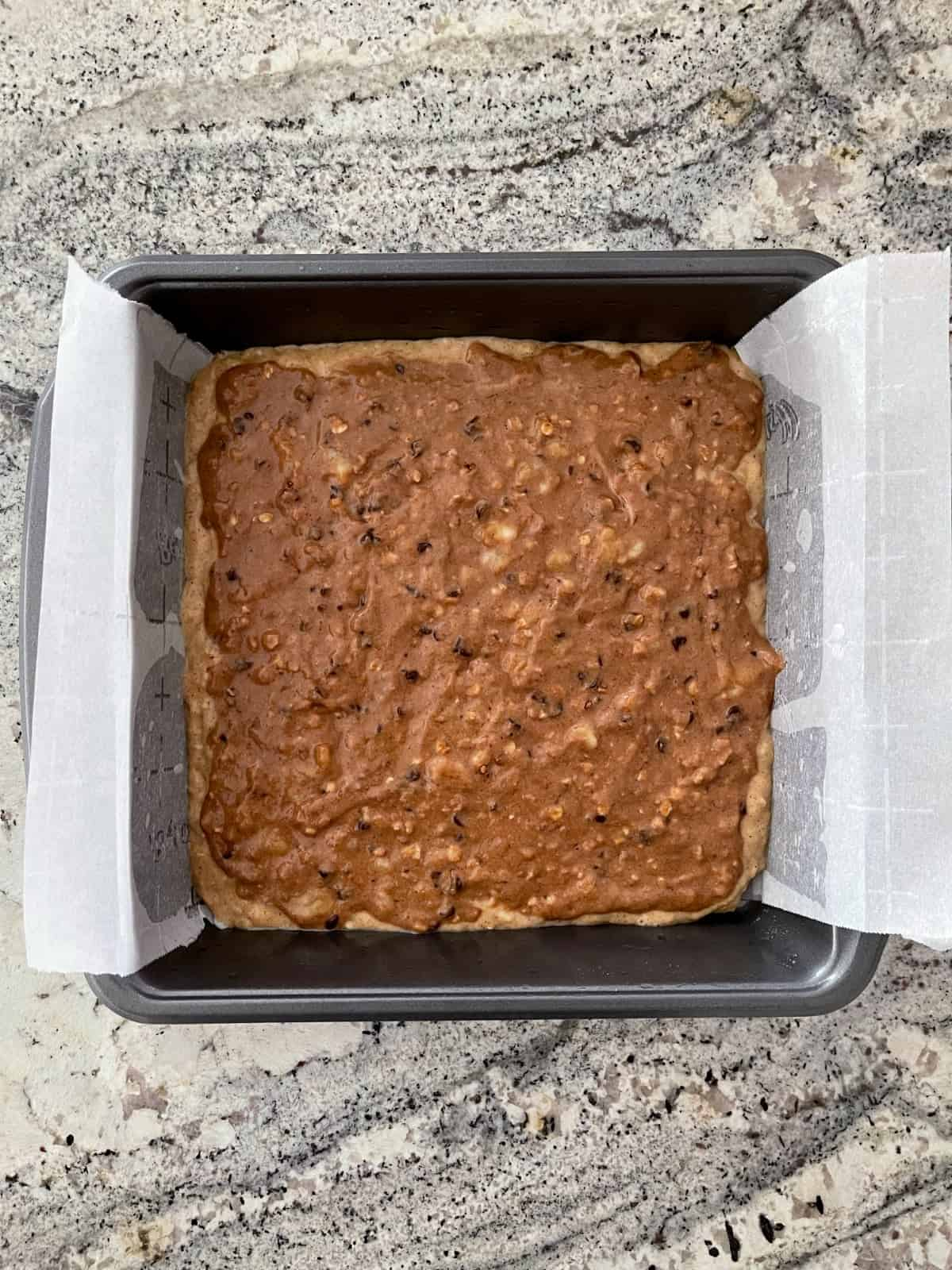 Unbaked banana bread brownies in parchment lined baking pan on granite counter.