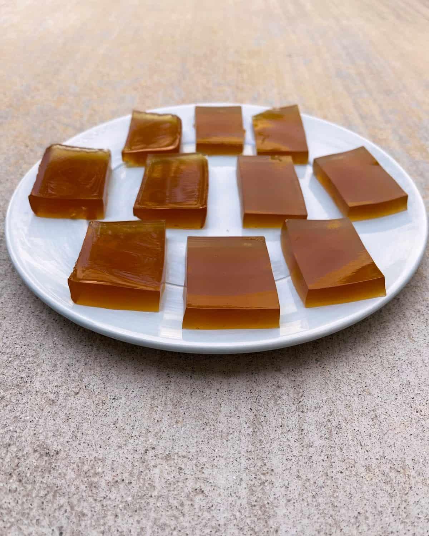 Apple cider vinegar jello blocks on light blue plate.