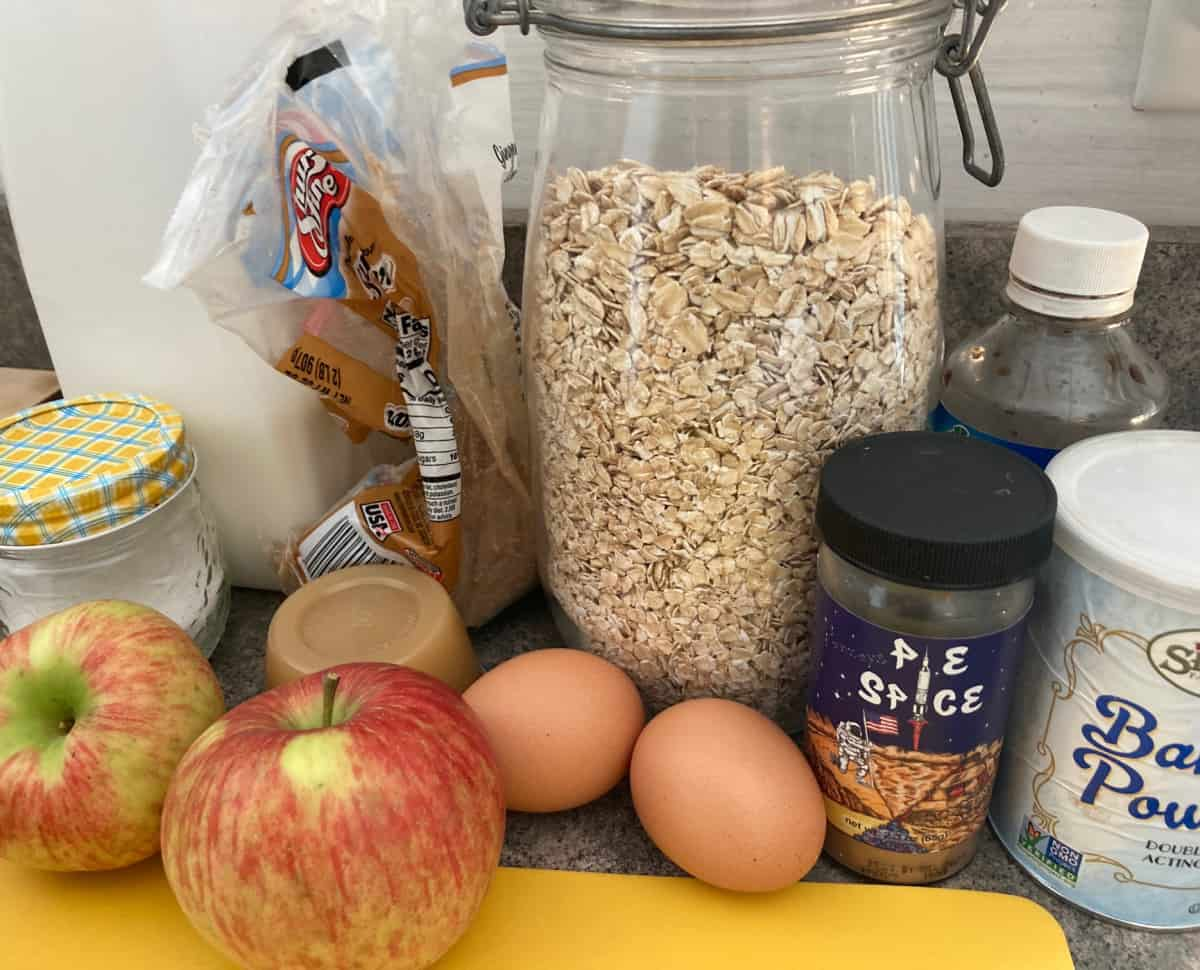 Ingredients for baking including rolled oats, brown sugar, baking powder, cinnamon salt, eggs and apples.